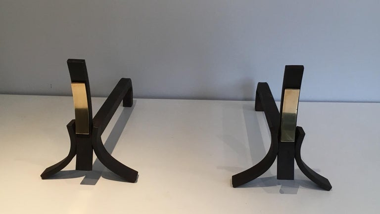 This pair of andirons is made of a convex brushed steel blade with a brass blade on its center. This is a French work, circa 1950.
