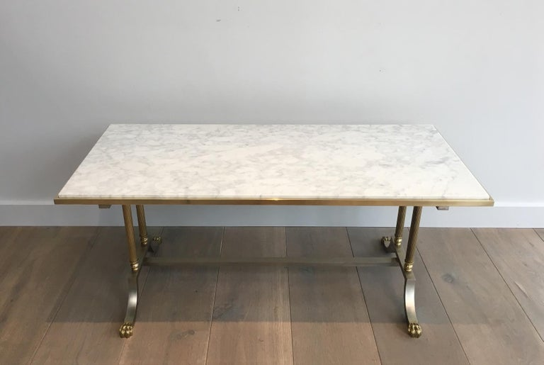 This very nice neoclassical coffee table is made of a brushed steel base with bronze claw feet and brass columns. The top is made of a white Carrare marble. This is a beautiful model from Maison Jansen. French, circa 1940.