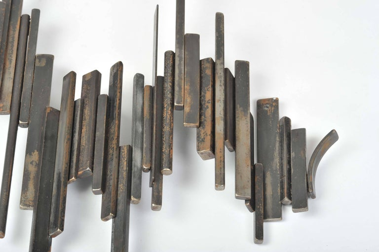 Large wall-mounted sculpture flows like a wave of sound. It is build up in rectangular segments of metal welded together. It is very decorative and suitable for inside or outside.