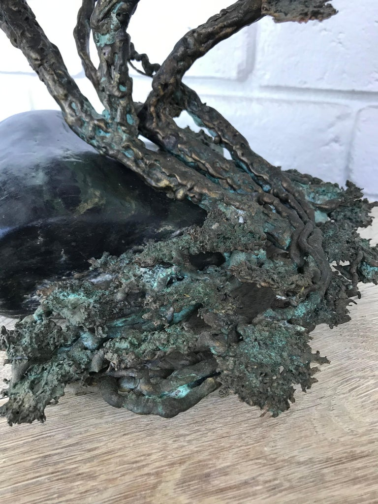 A brutalist style bronze bonsai tree sculpture.