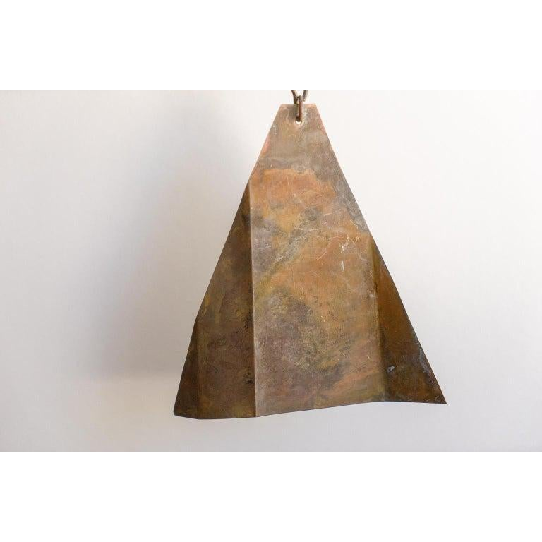 This Mid-Century Modern bronze wind chime retains its original finish and was created by the Italian-born artist Paolo Soleri. Soleri designed and created this piece in his Cosani workroom in Arizona.