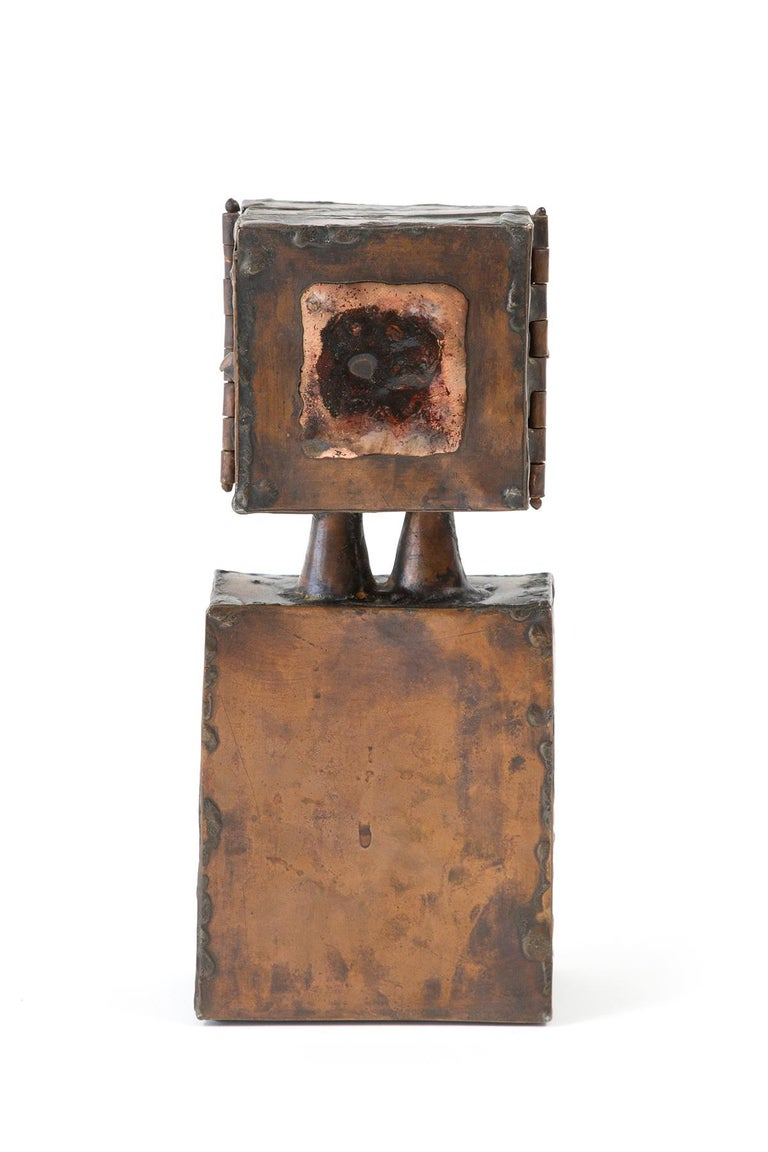Copper and enamel sculpture with a signature by artist David Laughlin features a hinged top portion that reveals a modernist face, a circular abstracted cut-out and an open circle in the centre when both sides are opened. The hinged doors, when