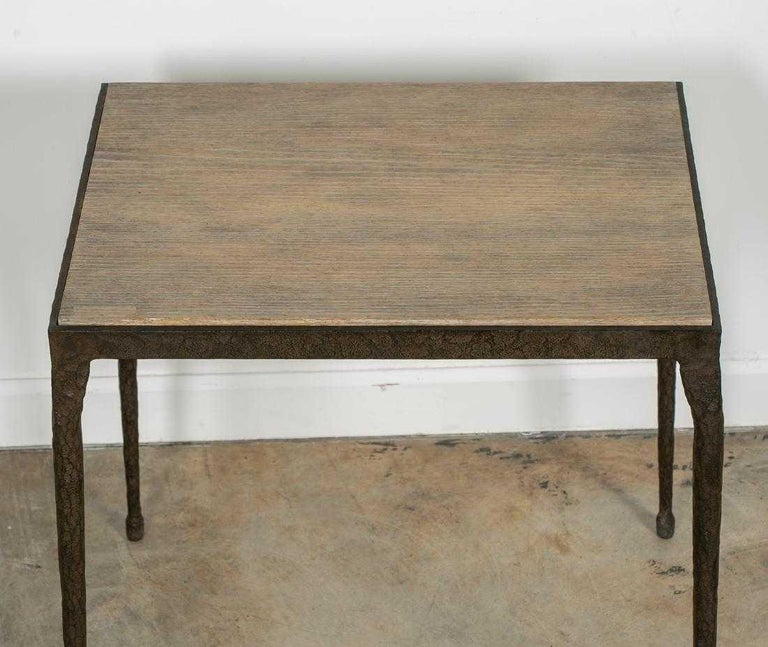 A Brutalist-style table with iron sculpted legs and light gray faux bois composite inset top. The light tonal composite top is in contrast to the roughly textured iron legs that taper to a delicate foot, and all are reminiscent of Paul Evans. The