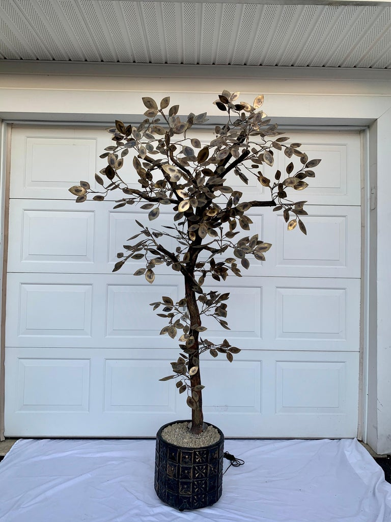 Mid-Century Modern metal tree sculpture by Curtis Jere. This tall dimensional botanic floor tree features torched gold brass metal leaves on natural wood stems and is anchored in a Brutalist planter. The planter has a built-in up light and natural