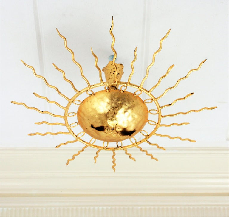 Magnificent Gold leaf gilt iron sunburst light fixture from the Brutalist period. Richly decorated by a layer of circles surrounding the central sphere, alternating short and long curly rays and a central flower decoration. Beautiful to place flush