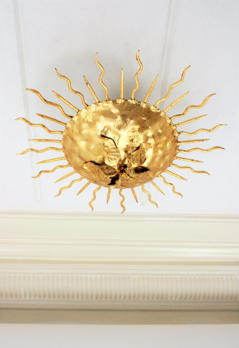 Gold leaf gilt iron sunburst light fixture from the Brutalist period. Richly decorated with the hammer marks at the central sphere, alternating straight and curly rays and a central flower decoration. Beautiful to place flush mounted or hanging from