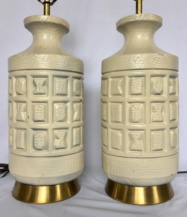 Mid-Century Modern Brutalist pottery table lamps. These cubist form table lamps feature sculptural matte cream pottery bases imprinted with geometric forms mounted on brass bases.   Measures: Height to Socket 22 inches. Height to Harp 30 inches.