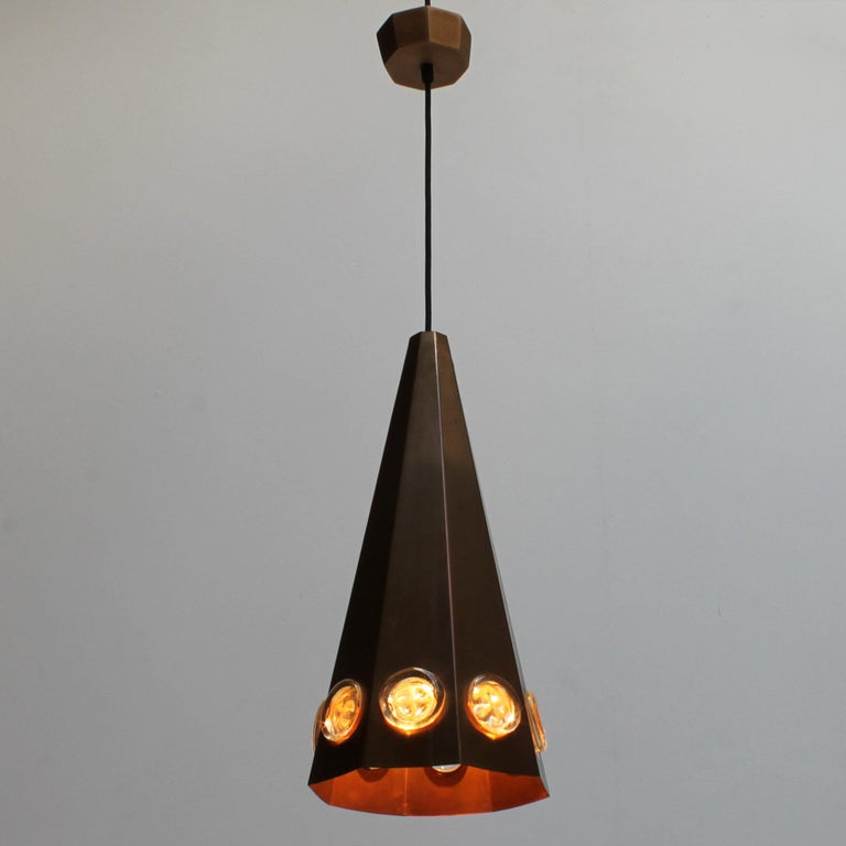 Brutalist Scandinavian pendant by Hans Bergström and Erik Hoglund for Ateljé Lyktan, Sweden. Conical shape in patinated copper and glass medallions.  Dimensions fixture: height 18.1 inches (46 cm), diameter 8.7 inches (22 cm). From ceiling till