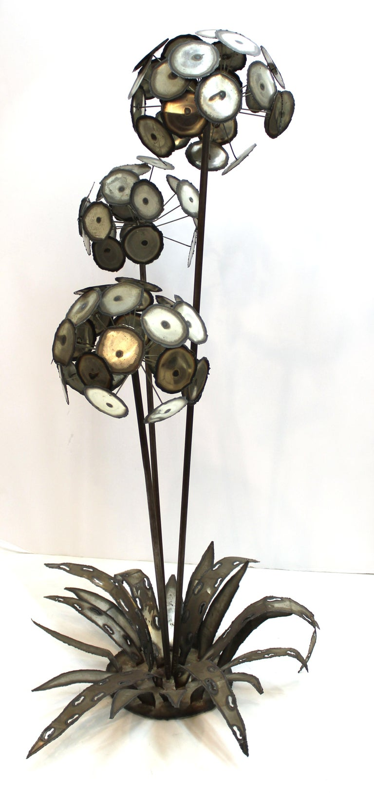 Brutalist monumental sized metal flower sculpture consisting of three flower heads on a base with leaves. One of the leaves has an illegibly signed metal tag. In good vintage condition with age-appropriate patina.