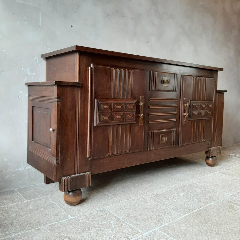 Brutalist style brown oak sideboard, credenza by Charles Dudouyt, 1940s-1950s. This midcentury cabinet features 2 large doors on each side, and in the middle 2 drawers with large storagespace inside. The doors and drawers panels are beautifully