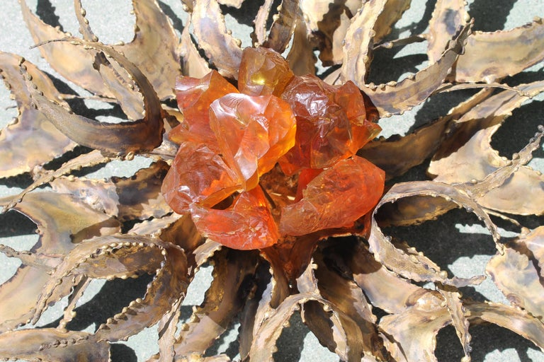 A brutalist metal wall sculpture by Bijan of Mexico in the form a sunburst, with orange Lucite chunks in the centre. Sculpture measures 26
