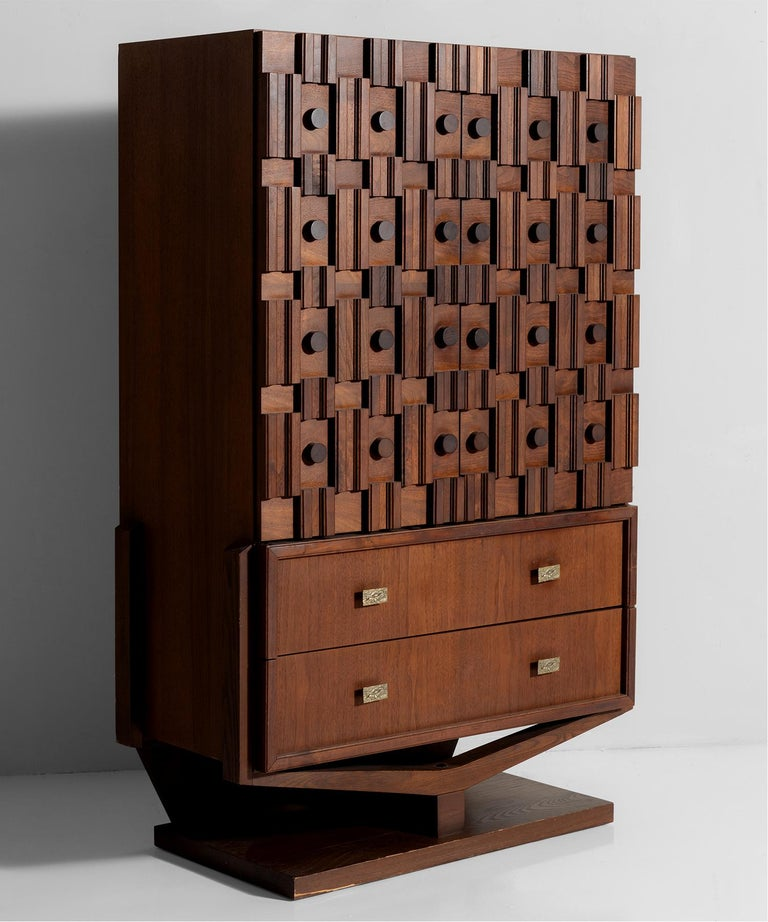 Raised on arched plinth with circular and beveled sculpted wood elements on side cabinet doors. Cast iron brutalist pulls.