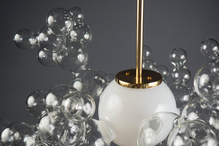 Single white glass globe surrounded by several bubble structures suspended from a 24-karat gold structure. Custom sizes and finishes available.
