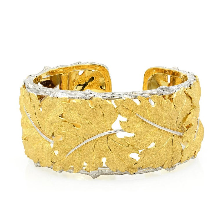 From designer Buccellati, this 18 karat white and yellow gold cuff bracelet is made up of textured yellow gold leaf motifs bordered by white gold bark edges. The cuff is hinged and measures 68x32mm. -18k White & Yellow Gold -Textured