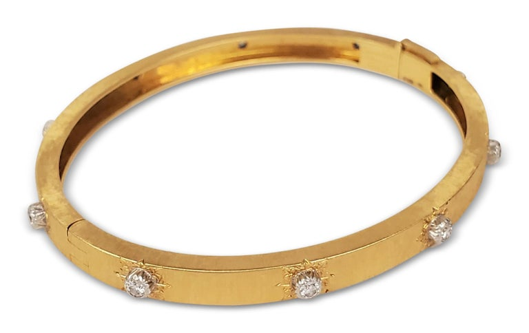 Authentic Buccellati 'Classica' bangle from the Macri collection is made in hand-engraved 18 karat yellow and white gold. The bracelet is set with 10 diamond stations of an estimated 0.48 cttw of round brilliant cut diamonds (E-F color, VS clarity).