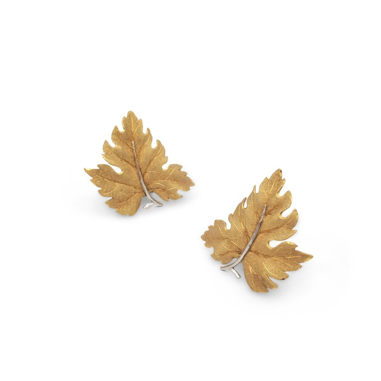 Authentic Buccellati earclips crafted in 18 karat yellow gold.  The detailed leaf design features a textured finish with white gold stems.  Earrings measure 2 inches in length by 1 3/4 inches in width.  Signed Buccellati, Italy, 750. CIRCA 2000s