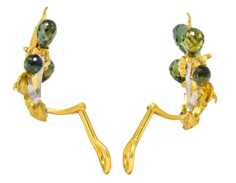 Earrings designed as sprouting foliate leaves featuring a matte gold finish with deeply engraved veining  With white gold vines topped by briolette cut sapphire, transparent medium-dark bluish-green to medium-light yellowish-green  Completed by