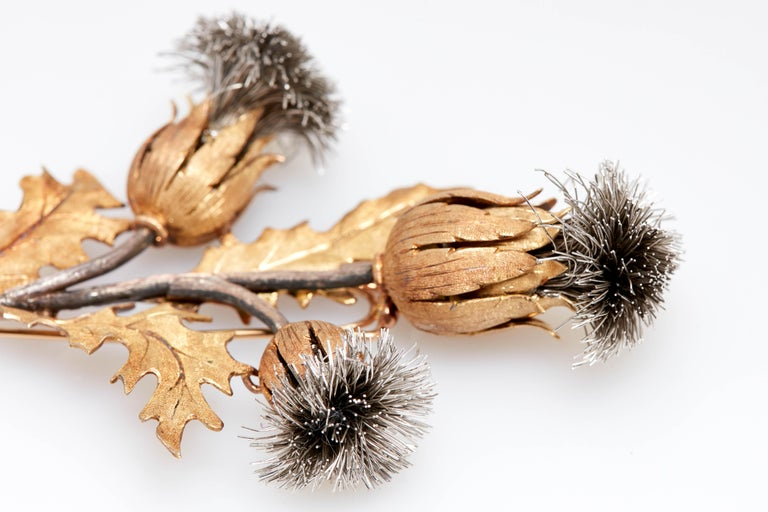 Large Mario Buccellati two-color gold and silver thistle clip-brooch. 18 kt, topped by three silver thistles with textured rose gold petals, supported by textured silver stem with textured gold leaves, signed M. Buccellati, approximately 27.4 dwts.