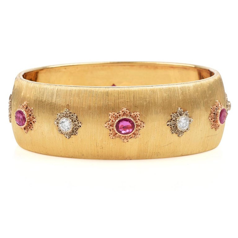 Compliment your wardrobe with this Expertly Executed Vintage 1960'sBuccellati Ruby and Diamond Cuff Braceletwith an approx total weight of 47.0 grams.  Crafted in solid 18K yellow gold, featuring the Rigato effect characteristic of the