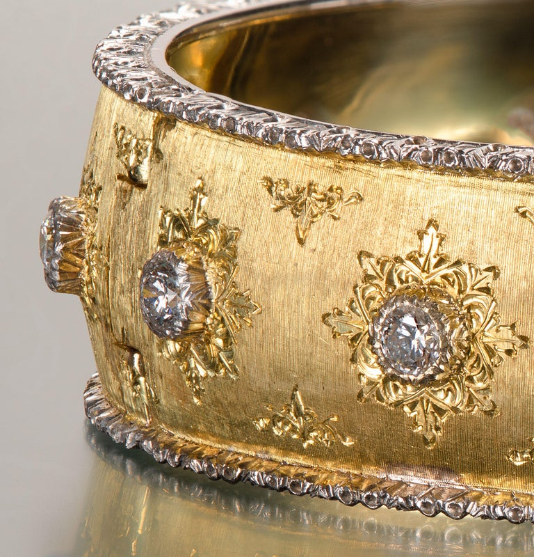 Yellow gold is finely hand-engraved in a fabric-like texture to create Buccellati's famed Florentine finish. This 18k gold bangle is decorated with full cut diamond melee set in 14k white gold with starburst engraving.  Inside circumference 6.625