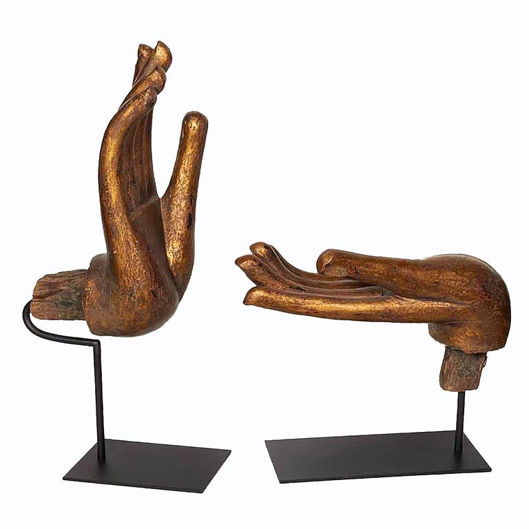 Two wooden Buddha hands, in gilt finish, each in a traditional gesture or mudra. Fingernails inlaid in mother of pearl. From Thailand, circa 1970. Mounted on black metal stands. Priced and sold separately. Dimensions of vertical hand shown