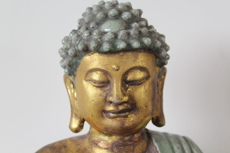 A tranquil light green glaze with gold leaf adorn this sitting Buddha statue in meditation position. Bringing happiness and good fortune this Buddha is seated with legs crossed with his right hand lowered, long fingers joining downward in the earth
