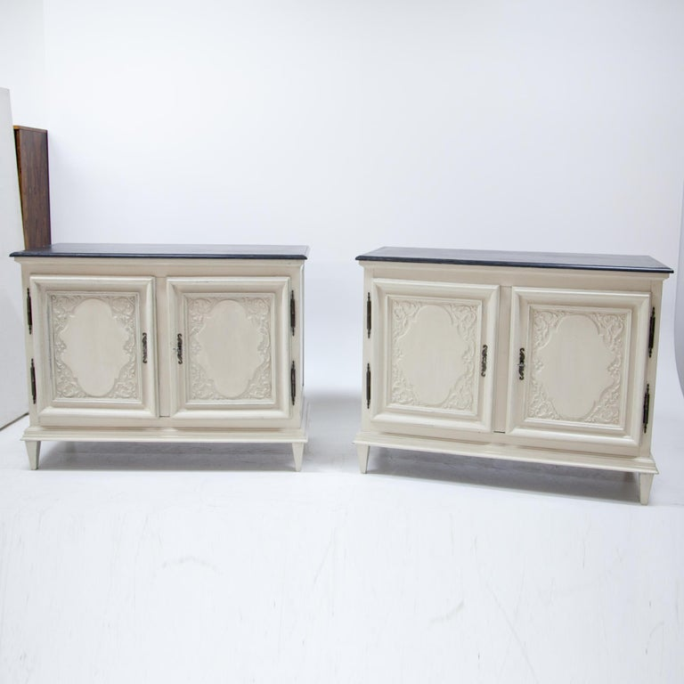 Pair of two-doored buffets out of solid walnut, standing on tapered legs. The buffets are decorated with profiled edges and fillings with carved vines and wavy medallions. The crème and grey paint is new and has a slight distressed look to it. Legs