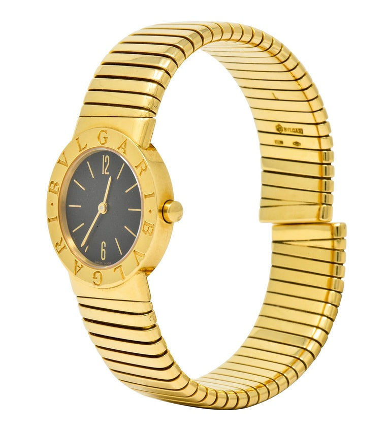 Flexible cuff style bracelet comprised of deeply ridged tubogas technology  Centering a sapphire crystal cover over a black watch face accented by gold hands and numerical markers  With a polished gold surround deeply engraved BVLGARI, twice