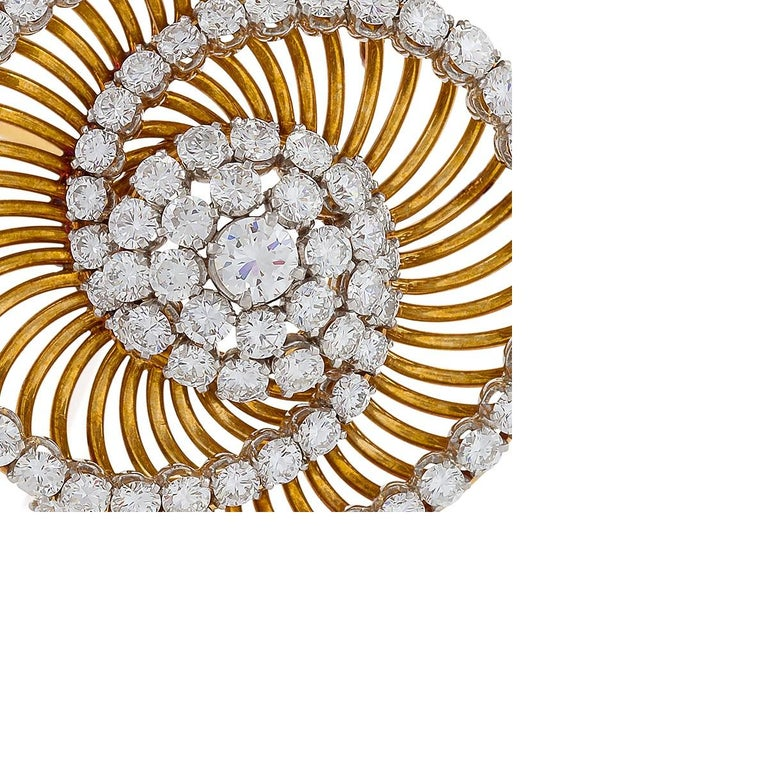 This intriguing brooch by Bulgari is set with six-and-a-half carats of round brilliant-cut diamonds, platinum set on a mount of yellow gold wire work. The dynamic, swirling form with intersecting arcs is designed as a pair of interlocking spirals