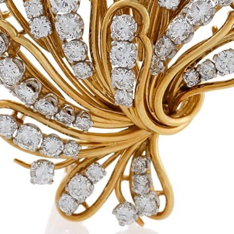 A  Mid-20th Century 18 karat polished gold brooch with diamonds by Bulgari. The brooch has 90 round-cut diamonds with an approximate total weight of 6.50 carats, H/I color, VS clarity. The dimensional, openwork brooch is designed in a floral motif.
