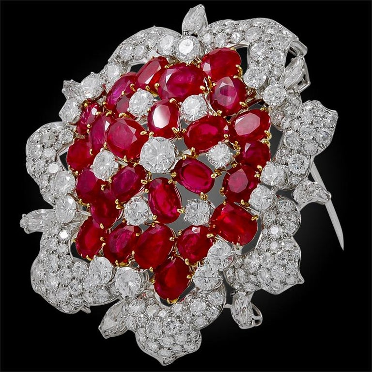 Comprised as a flower head, this resplendent Bulgari brooch is set with a myriad of radiant diamonds and Burma rubies, finely mounted in platinum.  Signed Bulgari.  25 Burma rubies weighing approx. 25 cts. with SSEF cert.