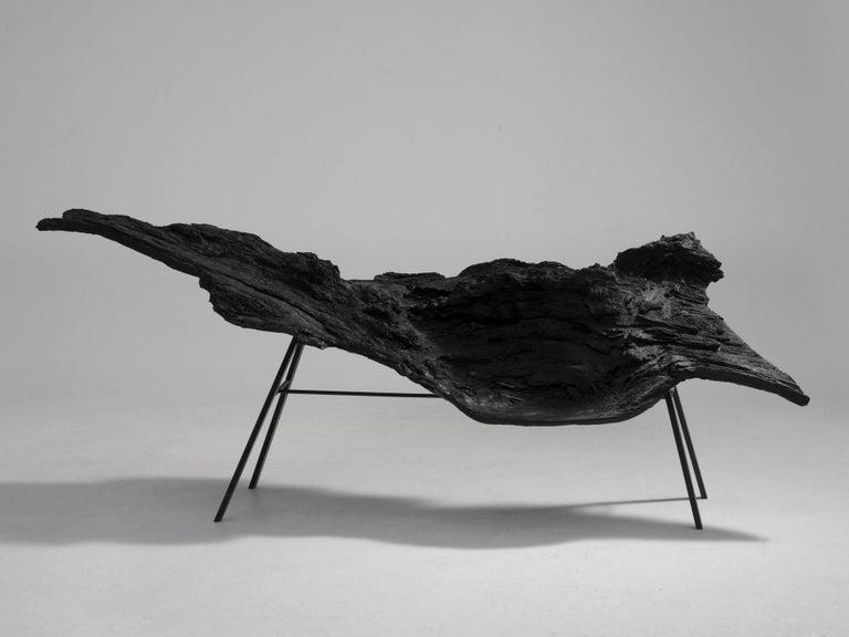 Sculptural bench in fiberglass on four metal legs.