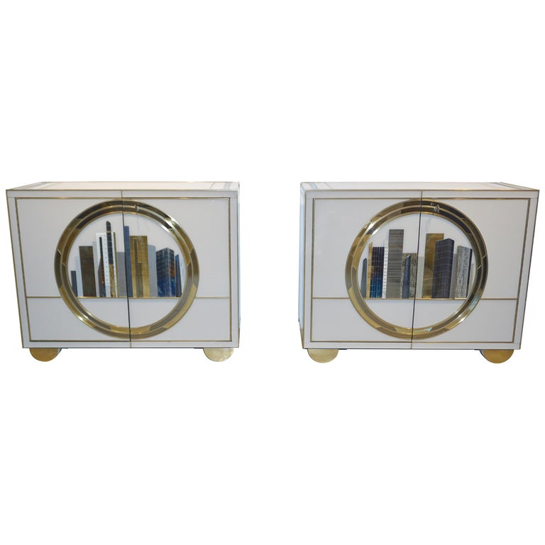 Pair of Italian fine design contemporary one-of-a-kind cabinets, entirely handcrafted with high quality execution. The surround is in cream white glass, each cabinet with an exceptional different decor in the front of a New York skyline glass