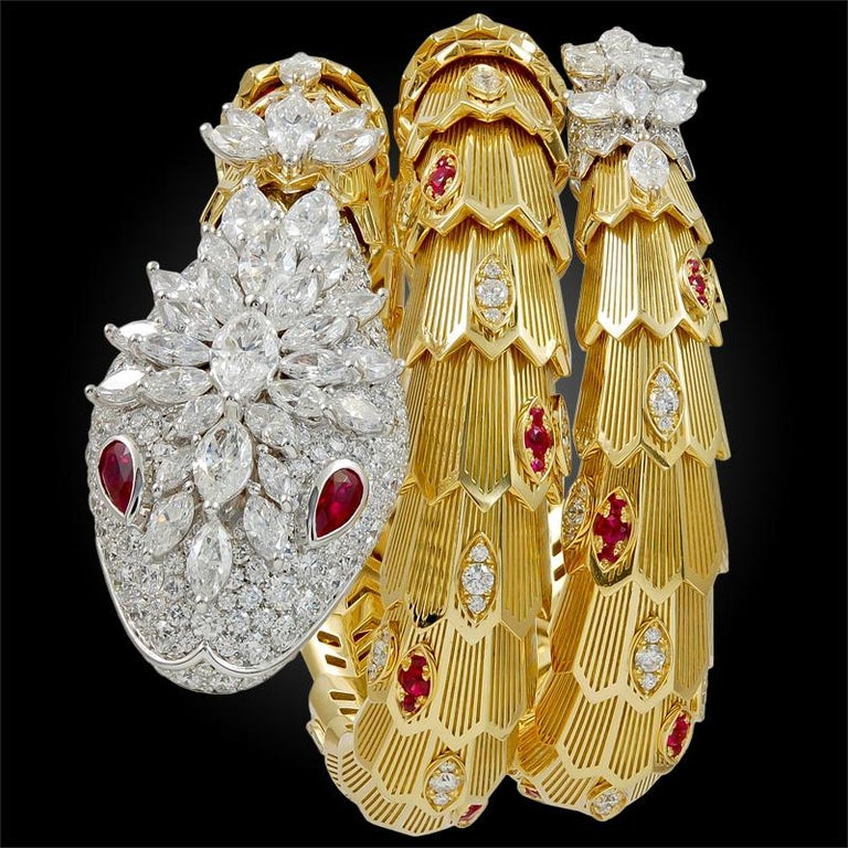 A phenomenal 18k white and yellow gold Bulgari serpenti bracelet that coils seductively around the wrist, designed with a pavé head of diamonds weighing approx. 9.70 carats, a radiant diamond crown finely set with 55 marquises weighing approx. 10.88
