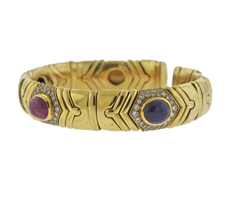 18k yellow gold cuff bracelet, crafted by Bulgari, featuring ruby (2.90ct), emerald (1.74ct) and sapphire (2.80ct) cabochons, surrounded with approx. 1.10ctw in G/VS diamonds. Bracelet will fit approx. 7.5