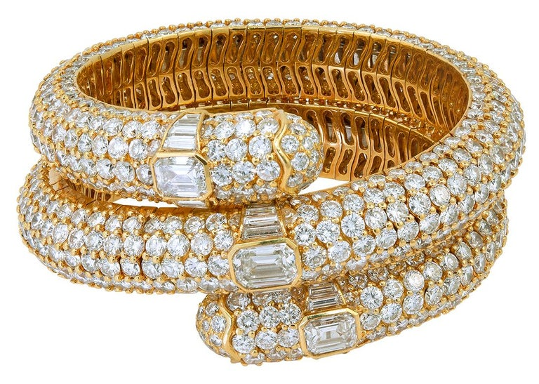 BULGARI Diamond Flexible Bracelet. An 18k yellow gold flexible band bracelet, set with brilliant step-cut and baguette diamonds signed Bulgari. emerald cut diamonds – approx. 1.35 cts., 1.68 cts. and 1.36 cts. inner-circumference approx. 6″ and it's