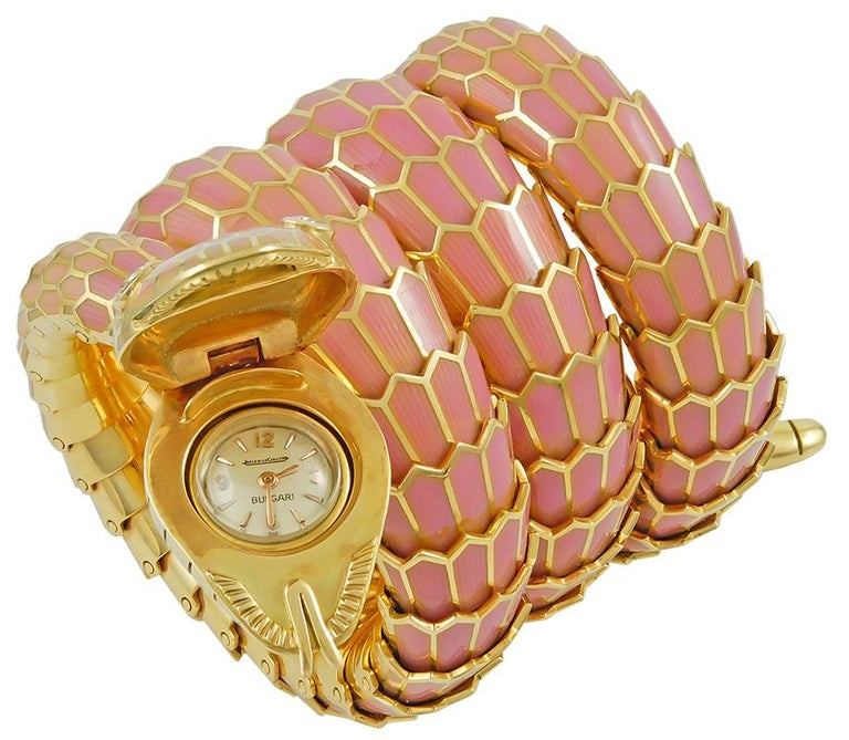 An exceptional 18k gold bracelet watch that captures the power and essence of  mystery and seduction through the iconic Bulgari serpent, which sensually coils around the wrist exposing its 18k gold and mauve pink enamel scales, the face enhanced