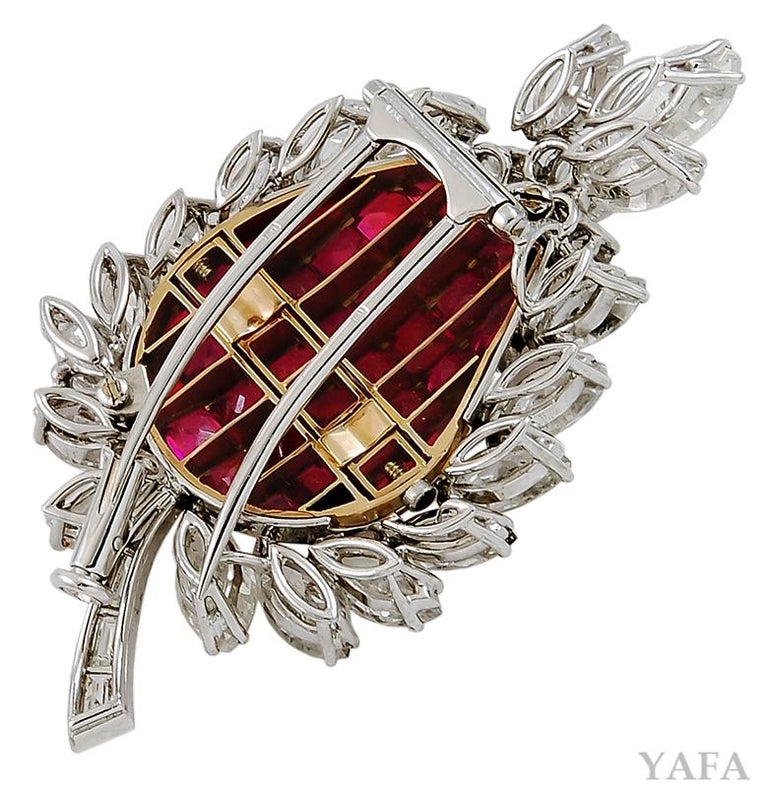 Designed as a leaf motif, this Bulgari Mystery-Set brooch centers upon several radiant calibré cut rubies with luminous marquise shaped petals that frame it, finely crafted in 18k gold and platinum. Signed Bulgari. Circa 1960's