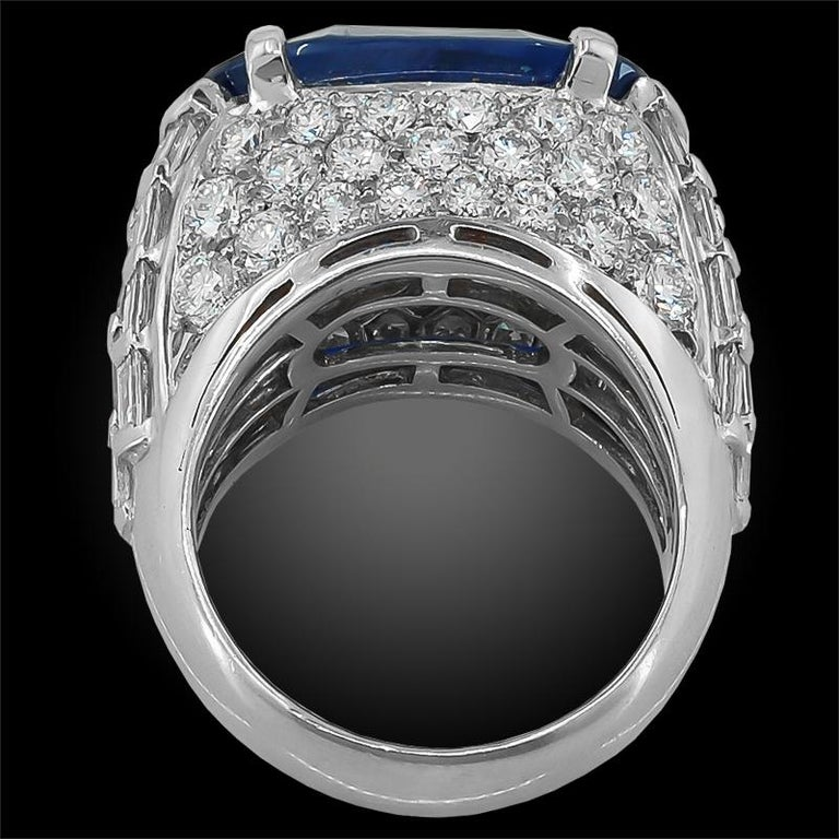 A fabulous ring by Bulgari, set at the center with an oval Ceylon No Heat sapphire of magnificent color, weighing approximately 13.68 carats with an AGL certificate. The sapphire is surrounded by square and step-cut diamond shoulders, pave set at