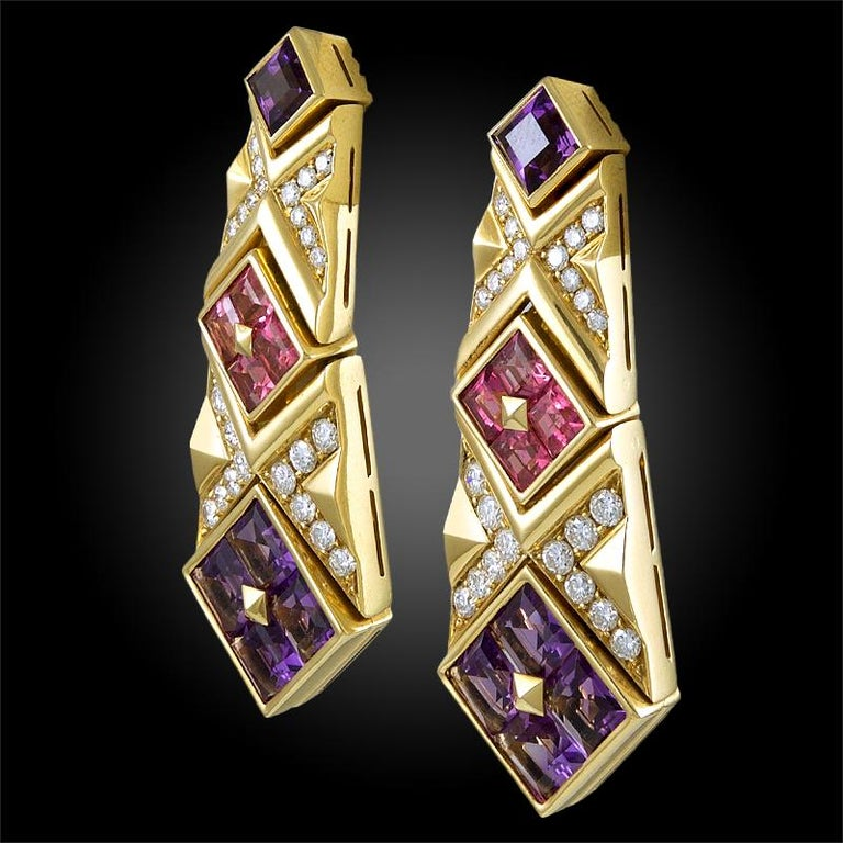 Exceptionally crafted by Bulgari, comprising a pair of uniquely designed hanging earrings that date back to the 1980's, each made of 18k yellow gold, set with vibrant amethysts and pink sapphires, further accented with brilliant round cut diamonds.