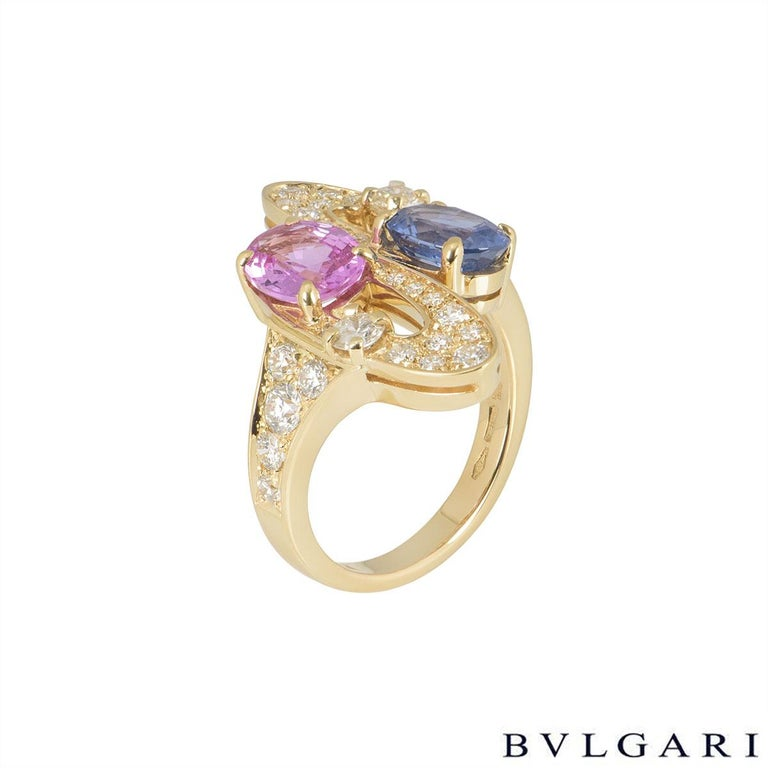 An 18k yellow gold diamond and multi-gem ring by Bvlgari. The ring is set with 2 oval shaped sapphires, one pink and one blue, surrounded by pave round brilliant cut diamonds half set on the band. The sapphires have an approximate total weight of