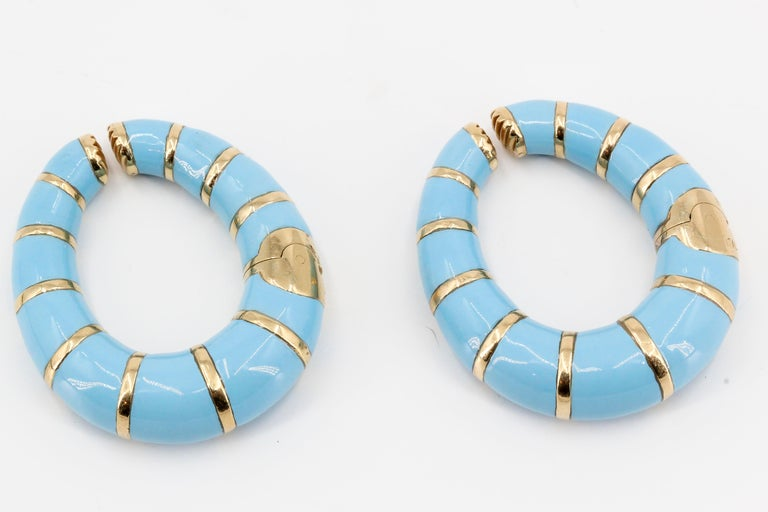 Stylish 18K yellow gold and enamel hoop earrings by Bulgari. They feature light blue enamel over yellow 18K gold body. Opening mechanism consists of a spring, so you can pull the two ends apart and slide it onto your ear. The earrings were designed