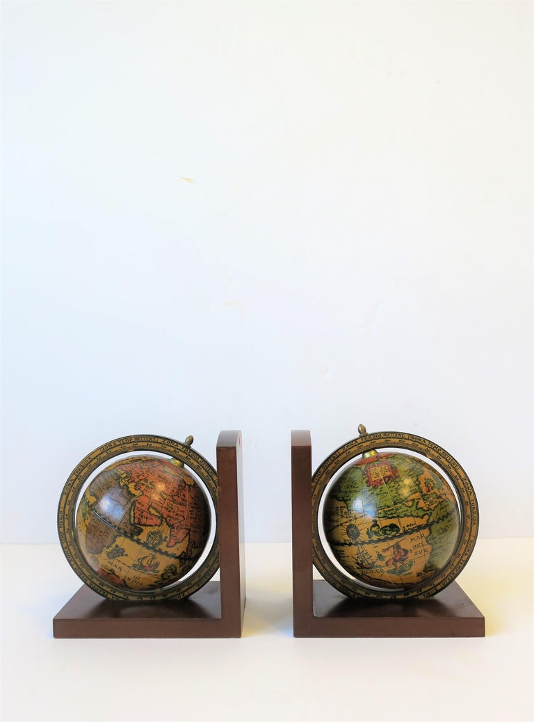 A midcentury pair of Italian world globe bookends with brass accents.