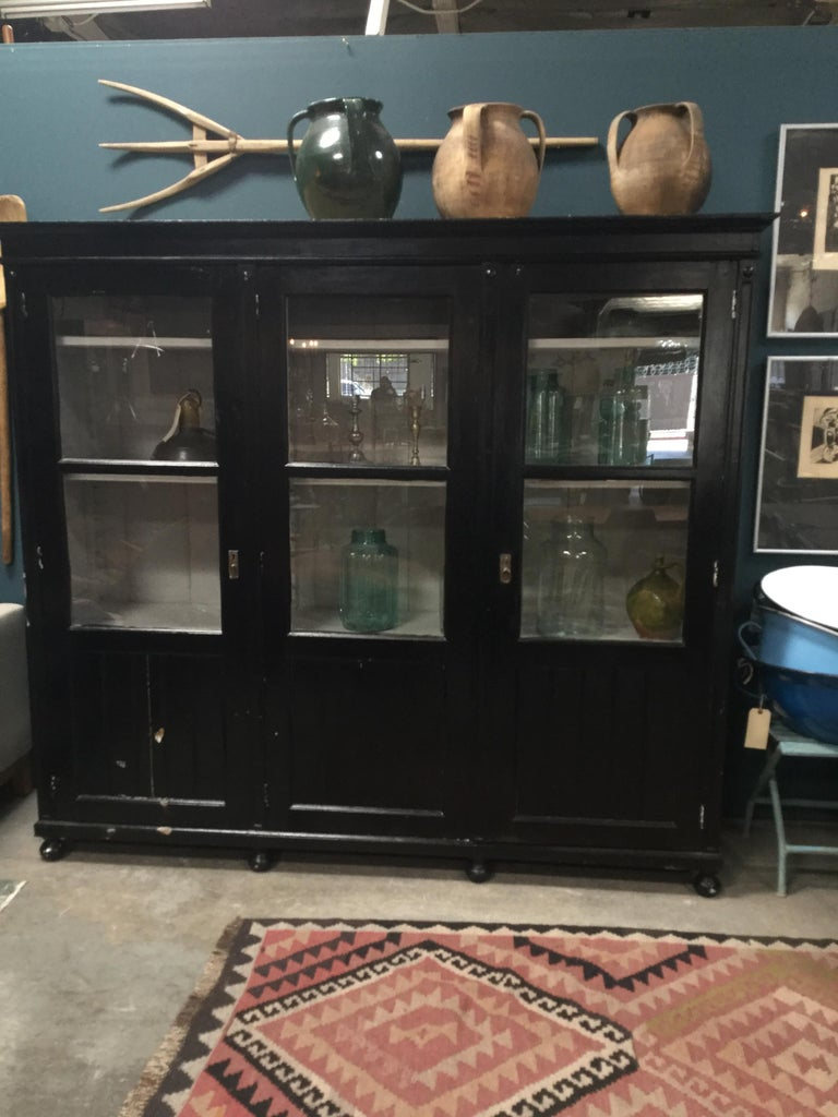 Beautiful black antique European hutch. Has three door-like cabinets, metal accents, and rounded feet. Comes with original key! Simple and classic. A perfect fit for almost every space.