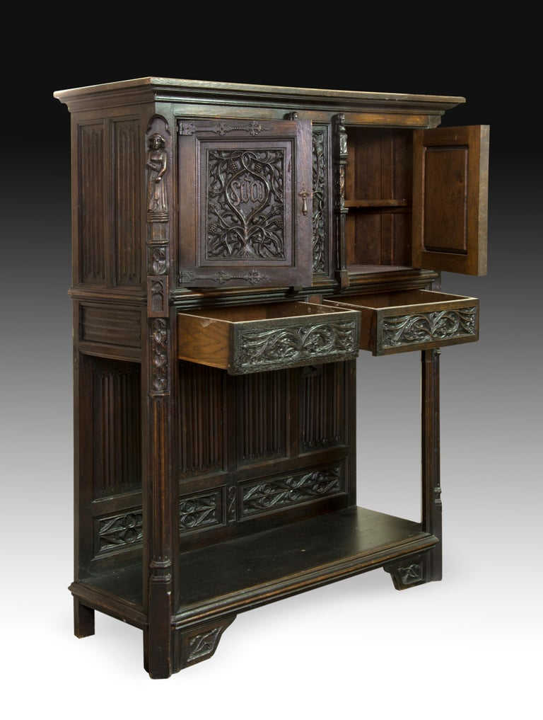 Typologically, the present piece has a shape that recalls certain Renaissance works (especially the buffet) with variations already customary in pieces of the 19th century. As for the decoration, centred on the front, the influence of Spanish Gothic