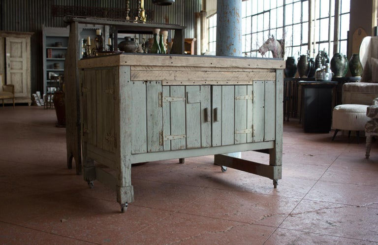 Early 20th century English industrial woodworker's cabinet. It has double doors on all sides. It is striking with its old scraped back paint and antique Welsh slate top. Perfect piece for a kitchen or bathroom. We have added casters.