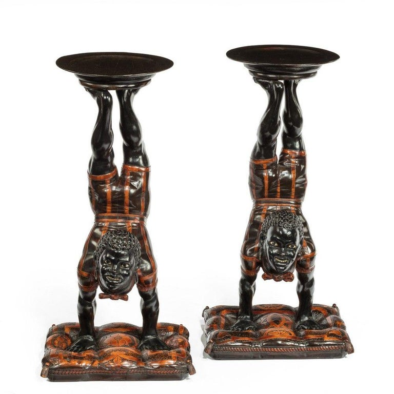 A pair of mid-19th century exceptional Venetian blackamoor side tables, The ebony and boxwood figures depicted as acrobats, wearing striped costumes and performing handstands on cushions with dishes balanced on their feet. Resting on ebonized