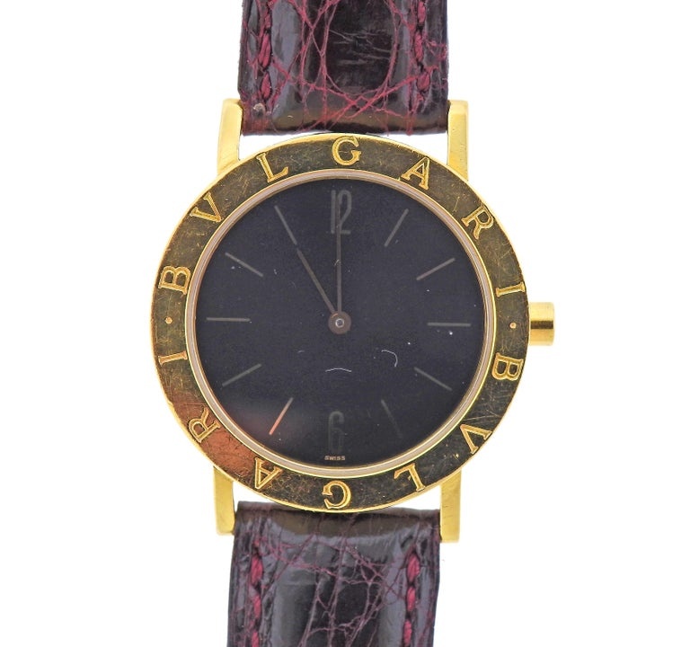 Classic 18k yellow gold Blvgari watch, with black dial, featuring gold stick markers. With leather band and  18k gold buckle. Case is 33mm in diameter, Bracelet is 6 7/8