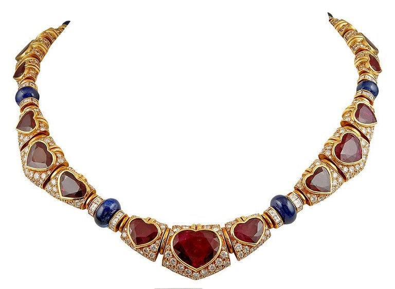 Vintage 18k yellow diamond necklace, designed as a series of links pave-set with brilliant-cut diamonds, set at the center with graduated heart-shaped rubies and cabochon sapphires. The bracelet, earrings and ring of similar design, signed Bvlgari.