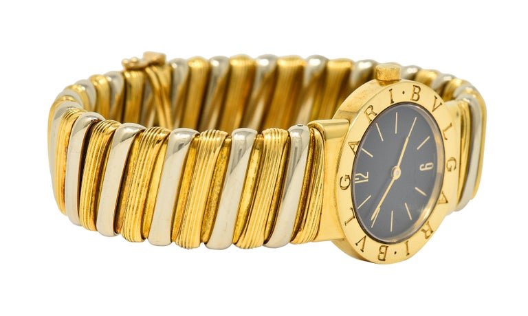 Springy cuff bracelet is comprised of polished white gold links alternating with ribbed gold links  Centering a sapphire crystal cover over a black watch face accented by gold hands and numerical markers  With a polished gold surround deeply